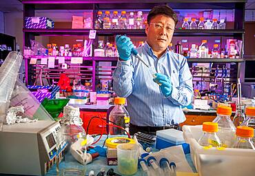 Male scientist in lab using pipette surrounded by lab equipment.