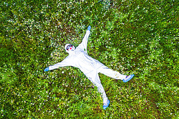 Person with a safety suit lying down in a flowers carpet in a forest area. Ayegui, Navarre, Spain, Europe