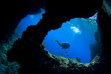 A diver swims past Boo Windows on Boo Island, Raja Ampat, West Papua, Indonesia, Pacific Ocean