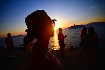 People enjoying views of Mykonos town at sunset, Greece