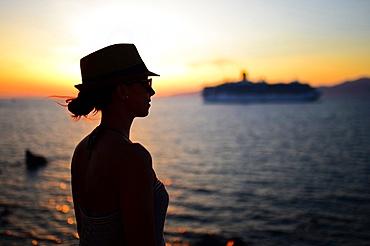Young woman enjoying views of Mykonos town at sunset, Greece