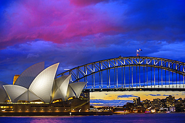 World famous Sydney Opera House and Harbour bridge at sunset. Blurred clouds and lights of landmarks reflect in blurred waters of Harbour. Sydney, New South Wales, Australia