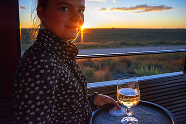 A waitress serving South African wine in The Rovos Rail luxury train travelling between Cape Town and Pretoria in South Africa Pride of Africa beautifully rebuilt Classic train that form part of the luxurious and privately owned Rovos Rail fleet