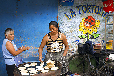 Mayan women baking tortillas in the streets of Antigua, Guatemala, Central America. La Tortolita.