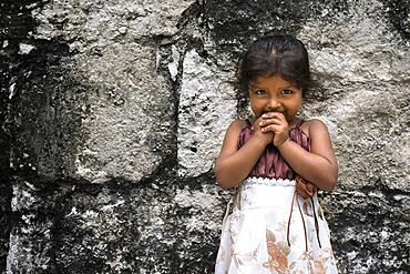 Local Girl in Tikal Pyramid ruins (UNESCO site), Guatemala. Great Jaguar Temple (Temple I) Pre-Columbian Maya Site at Tikal, El Peten National Park, Guatemala, a UNESCO World Heritage Site