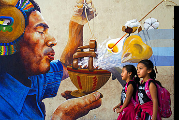 Two girs walking in front of a wall panting in San Juan La Laguna, Solol√°, Guatemala. Traditional mayan painting art Santiago Atitlan, lake Atitlan, Guatemala.