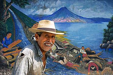 Local man walking in front of a wall panting in San Juan La Laguna, Solol√°, Guatemala. Traditional mayan painting art Santiago Atitlan, lake Atitlan, Guatemala.