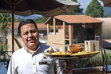 Waiter with the breakfast in Filadelfia coffee estate, R. Dalton Coffee Company, Antigua, Guatemala.