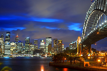 Side view of Sydney Harbour bridge architectural landmark and city at sunset. Illuminated arch of the bridge reflecting in blurred waters Sydney, New South Wales, Australia