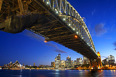 Side view of Sydney Harbour bridge Opera House and city CBD at sunset. Illuminated arch of the bridge reflecting in blurred waters Sydney, New South Wales, Australia