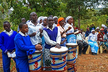 Playing drums in a funeral for the death of a person due to Coronavirus and AIDS in a small village near Kitui city in the Kamba country in Kenya, Africa.