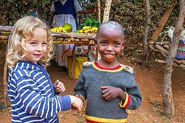 European blonde girl giving the hand and sharing with a black children boy in the primary and second school in a small village near Kitui city in the Kamba country in Kenya, Africa.