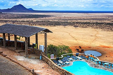 Guests looking over swimming pool to savannah, Voi Safari Lodge, Tsavo East National Park, Coast, Kenya. Elephants at a waterhole in front of Voi Safari Lodge Tsavo East National Park Kenya East Africa