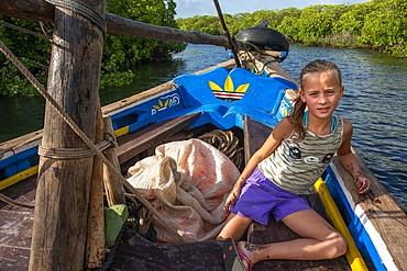 European tourists girl in a dhow sailing through Makanda Channel, Lamu archipelago, Kenya. Red mangroves along coastline of Manda Island