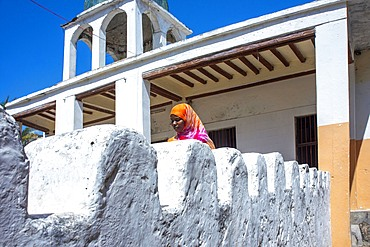 Swahili woman and white house in the city town of Lamu in Kenya