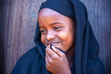 Funy swahili girl portrait in the strees of the city town of Lamu in Kenya
