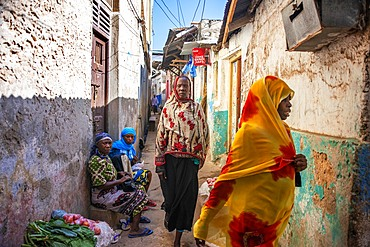 Swahili women with colorful veils in the strees of the city town of Lamu in Kenya