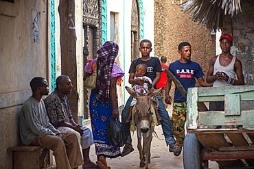 Men riding donkeys on the main street of Lamu town in Lamu Island, Kenya.