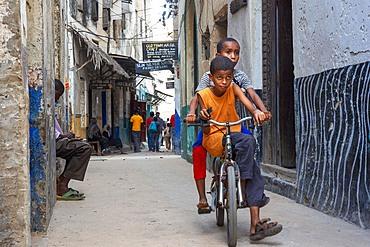 Boys riding on a bicycle in a narrow street of Lamu town in Lamu Island, Kenya.