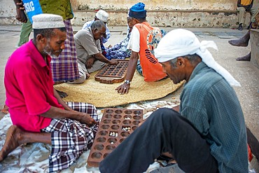 Group of Musilm men playing awale or Bao wearing traditional clothes enjoy leisure time in Lamu island town