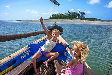 Tourists european girls inside a dhow sailing boat in Lamu archipelago, Kenya.