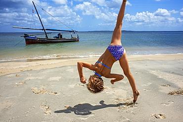 European Tourist girl doing acrobatic jumps on the white beach in Manda island in Lamu archipelago in Kenya
