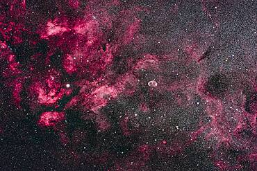 This is the central area of Cygnus and its bright Milky Way starcloud surrounded by red nebulosity. At left is the star Sadr (gamma Cygni) with the complex of nebulosity catalogued as IC 1318. At centre is the distinct Crescent Nebula, NGC 6888, a expanding nebula created by winds from a hot Wolf-Rayet star.  At bottom left is the star cluster Messier 29,  though looking a little lost in the rich starfields here. At top is the cluster IC 1311, looking more obvious than M29 but not observed visually and included in the NGC catalog. Odd. At far right are the large and loose star clusters NGC 6883 and NGC 6871, the latter an obvious binocular sight. To the left of Sadr is the small cluster NGC 6910. The dark nebulas B145 and LDN 862 are at right. The small emission nebula at bottom is Sharpless 2-104.