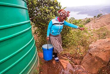 Woman carrying a bucket over rocky terrain in the Hhohho region of Swaziland, Africa.