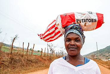 Woman carrying a bag of potatoes on her head down a dirt road in the Hhohho region of Swaziland, Africa.