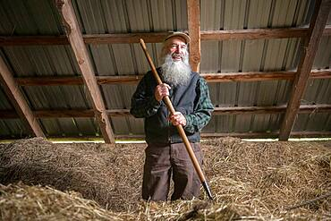 Portrait of a farmer inside a bard filled with hay in Harrison, Maine