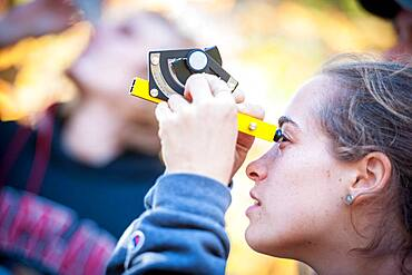 Student using a clinometer to measure the height of a tree.