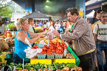 A vendor sells produce to a customer at a farmers market in Baltimore,MD