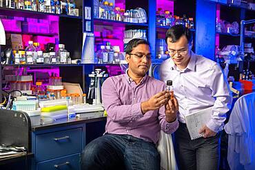 Two men examine beaker together while in lab, Beltsville, MD