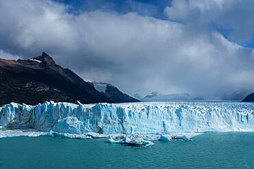 The jagged face of Perito Moreno Glacier and Lago Argentino in Los Glaciares National Park near El Calafate, Argentina.  A UNESCO World Heritage Site in the Patagonia region of South America.  Icebergs from calving ice from the glacier float in the lake.  Behind at left is Cerro Moreno.