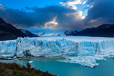 The jagged face of Perito Moreno Glacier and Lago Argentino in Los Glaciares National Park near El Calafate, Argentina.  A UNESCO World Heritage Site in the Patagonia region of South America.  Icebergs from calving ice from the glacier float in the lake.  In the distance at left is Cerro Gardener.