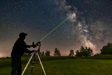 Me aiming the A&M 80mm refractor on the Astro-Tech Voyager mount at the Milky Way with its laser pointer finder showing the way. I am aiming at M11 in Scutum.