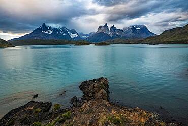 The rocky shoreline of Lago Pehoe in Torres del Paine National Park, a UNESCO World Biosphere Reserve in Chile in the Patagonia region of South America. Across the lake is the Paine Massif in the low clouds.
