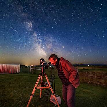 Mark gazing at a target, M22, in the Milky Way with his TeleVue 127 refractor at the annual Rothney Observatory Milky Way Nights for July 25, 2019. Several satellite trails mark the sky. Jupiter (brightest at right) and Saturn (at left) flank the Milky Way.