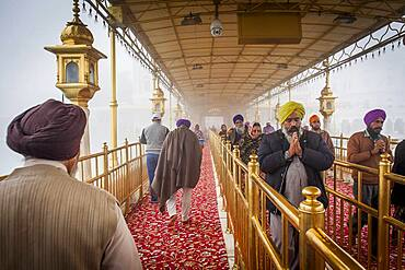 Devotees at causeway to Golden temple, Amritsar, Punjab, India