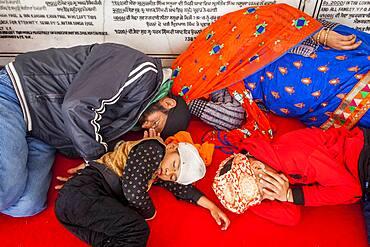 Pilgrims (family) sleeping, after a hard trip, inside of Golden temple, Amritsar, Punjab, India