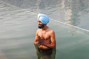 pilgrim bathing in the sacred pool Amrit Sarovar, Golden temple, Amritsar, Punjab, India
