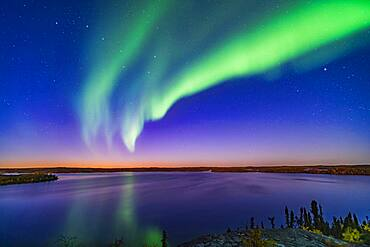 An arc of Northern Lights appears in the evening twilight over Prelude Lake near Yellowknife, NWT, on September 9, 2019. The Big Dipper is at left. Capella is at right.