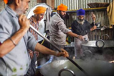 Volunteers cooking for the pilgrims who visit the Golden Temple, Each day they serve free food for 60,000 - 80,000 pilgrims, Golden temple, Amritsar, Punjab, India