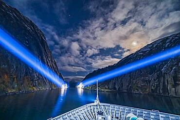 Exiting the narrow Trollfjord by searchlight and under moonlight, on the northbound voyage of the Hurtigruten ferry ship the ms Trollfjord, on October 15, 2019. Capella is at top; Betelgeuse and Orion are rising at centre at the mouth of the fjord; Aldebaran is partly in cloud left of the Moon.