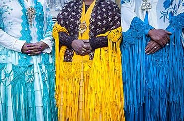Detail of dresses and hands. At left Benita la Intocable , in the middle Angela la Folclorista, and at right Dina, cholitas females wrestlers, El Alto, La Paz, Bolivia