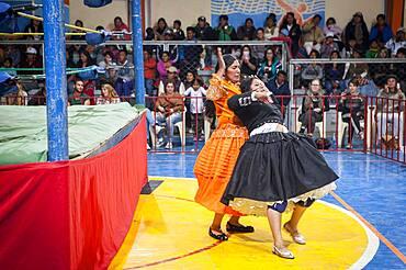 Lucha Libre. Combat between Dina with orange dress and Julieta, cholitas females wrestlers ,Sports center La Ceja, El Alto, La Paz, Bolivia
