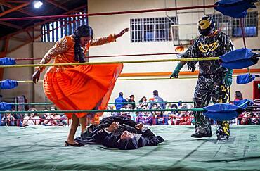 Lucha Libre. Combat between Dina with orange dress and Julieta, cholitas females wrestlers ,with a referee, Sports center La Ceja, El Alto, La Paz, Bolivia