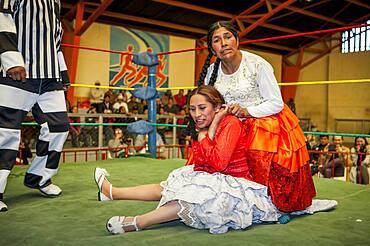 Lucha Libre. Combat between Dina with orange skirt and Benita la Intocable , cholitas females wrestlers ,with referee, Sports center La Ceja, El Alto, La Paz, Bolivia
