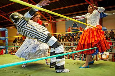 Lucha Libre. Combat between Dina with orange skirt and Benita la Intocable , cholitas females wrestlers ,with referee in the middle, Sports center La Ceja, El Alto, La Paz, Bolivia