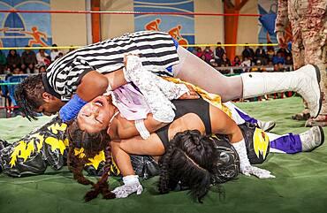 Lucha Libre. Julieta and Celia la Simpatica whith pink skirt during a crazy combat, agaist males wrestlers, Sports center La Ceja, El Alto, La Paz, Bolivia